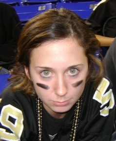 football jersey girl with beads on and streaks of black makeup on cheeks