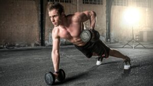 Fitness training. Muscular man holding weights in one armed plank positionpushing up